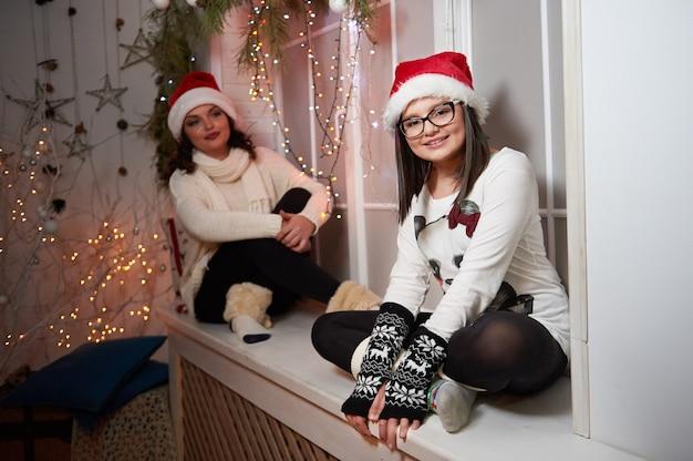 Glückliche mutter und tochter sitzen auf einer fensterbank an weihnachten e