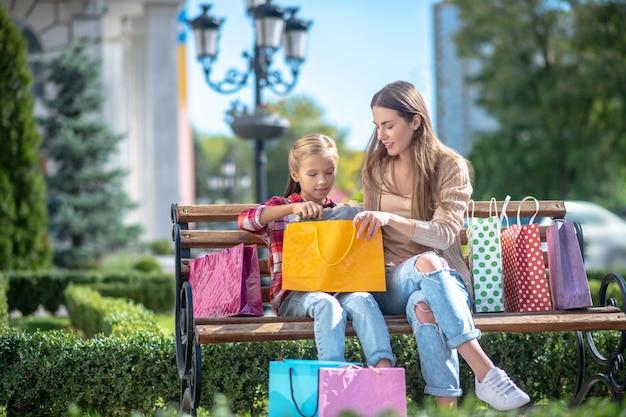 Glückliche mutter und tochter sitzen auf parkbank und nehmen gegenstand aus einkaufstasche heraus