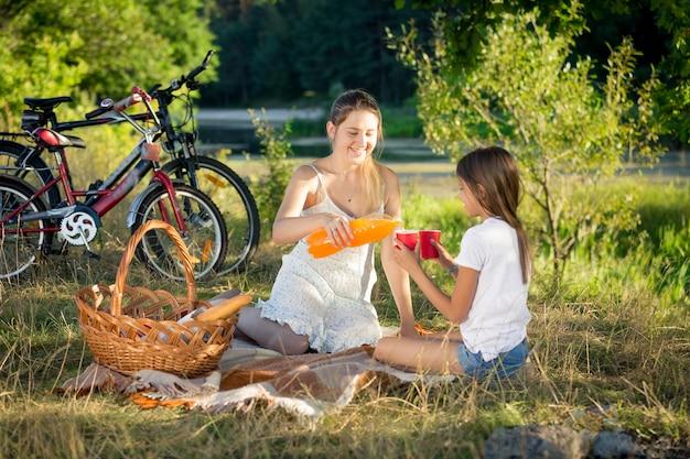 Glückliche mutter und tochter trinken orangensaft beim picknick