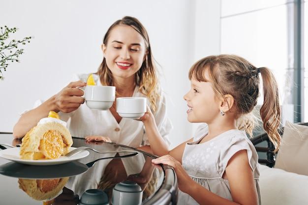 Glückliche mutter und tochter trinken tee und essen köstlichen kuchen mit orangenfüllung und schlagsahne