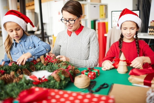 Glückliche mutter und töchter, die den weihnachtskranz schmücken