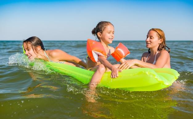 Glückliche mutter und zwei kleine positive töchter baden und schwimmen mit einer luftmatratze im meer