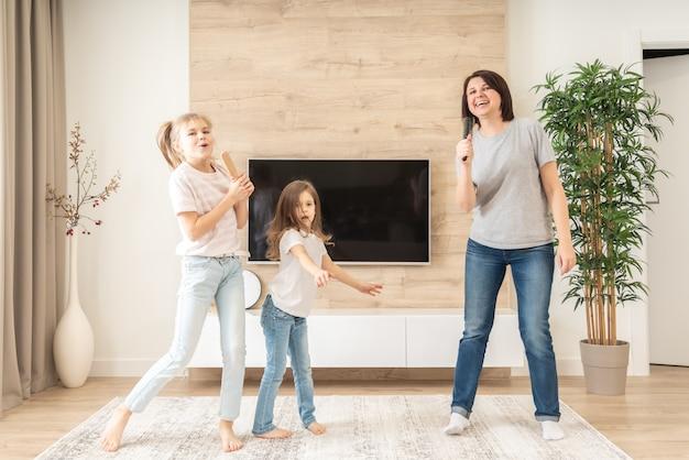 Glückliche mutter und zwei töchter, die spaß haben, karaoke-lied in haarbürsten zu singen. mutter lacht und genießt lustige lifestyle-aktivitäten mit teenager-mädchen zu hause zusammen.