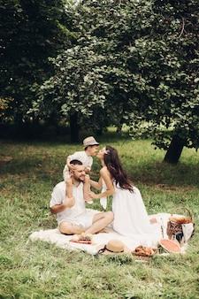 Glückliche mutter, vater und ihr süßer kleiner sohn machen picknick im sommerpark. kind sitzt auf den schultern seines vaters. familien- und freizeitkonzept