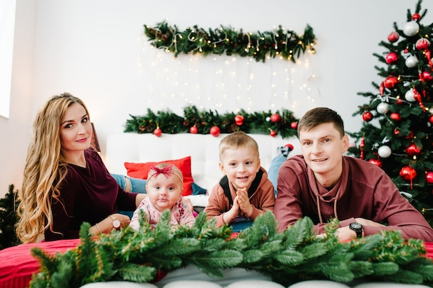 Glückliche mutter, vater und kinder nahe weihnachtsbaum