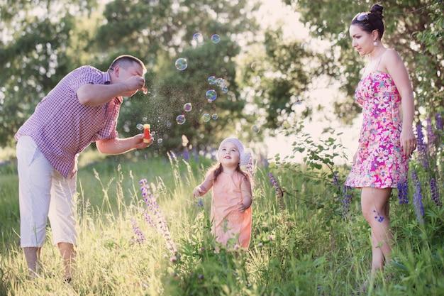 Glückliche mutter, vater und tochter blasen blasen im park