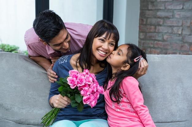 Glückliche mutter, welche die rosen geküsst von ihrer tochter hält