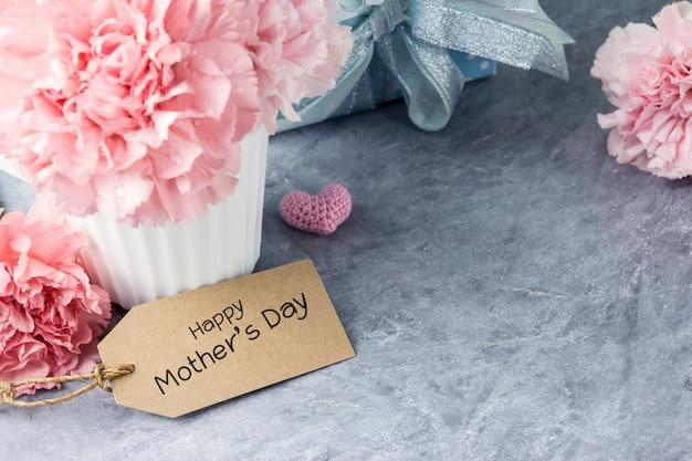 Glückliche muttertagmitteilung auf tag und rosa gartennelkenblume in der weißen schale