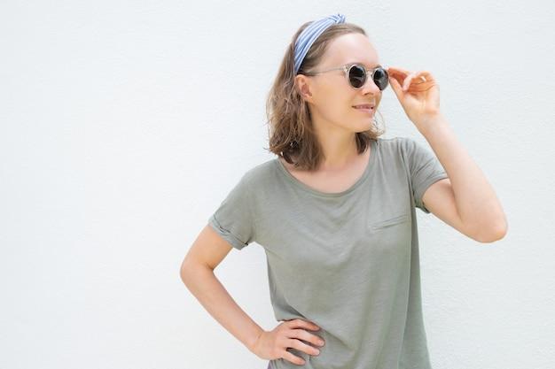 Glückliche nachdenkliche frau, die sommertouristenkleidung trägt