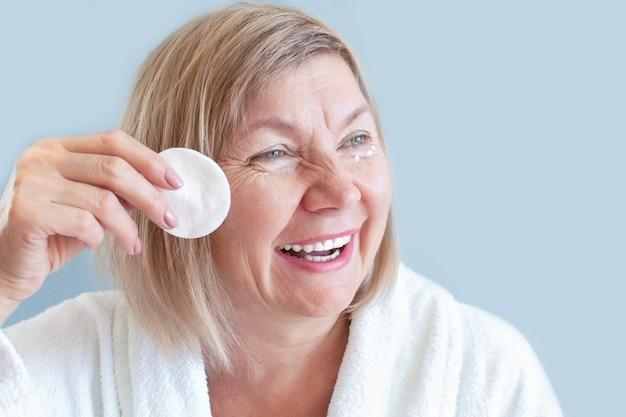 Glückliche natürliche frau seniora mit wattepad reinigt die haut. natürliche wellnessanwendungen zu hause, bio-kosmetik. anti-age-konzept, gesundheitswesen und kosmetologie, neue senioren, rentner und ältere menschen,