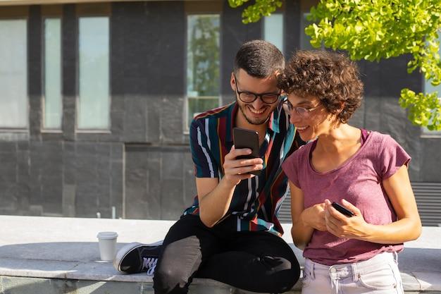 Glückliche nerdy paare, die lustigen inhalt am telefon aufpassen