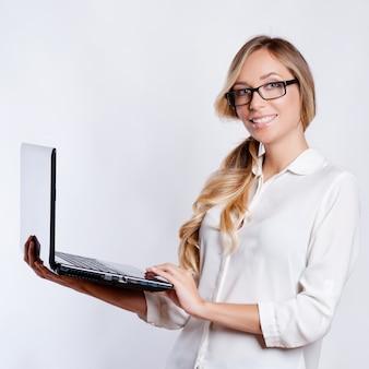 Glückliche nette frau, die leeren laptop-computer bildschirm über grauem hintergrund zeigt.