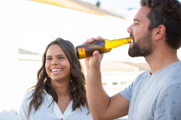 Glückliche nette lateinische frau, die bierparty mit freunden genießt