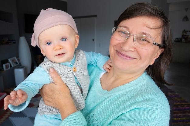 Glückliche neue großmutter, die mit niedlicher kleiner enkelin aufwirft