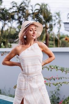 Glückliche niedliche romantische kaukasische frau im eleganten weißen kleid mit offenem rücken und strohhut