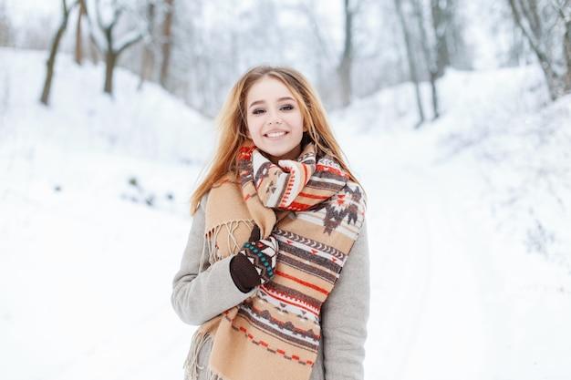 Glückliche niedliche stilvolle junge frau mit schönen braunen augen in einem trendigen grauen mantel mit einem vintage-wollschal in warmen mittaens steht in einem winterpark. schönes mädchen geht durch den wald.