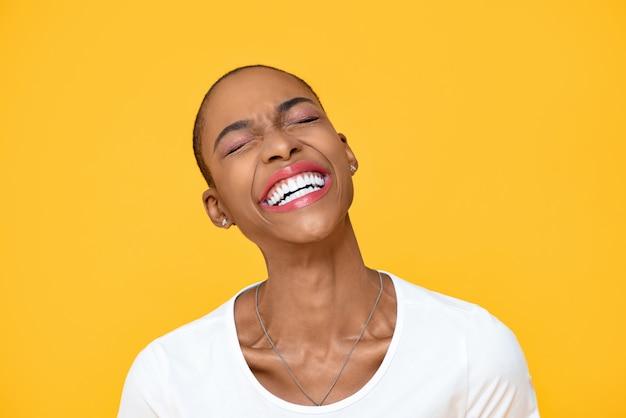 Glückliche optimistische afroamerikanerfrau, die mit geschlossenem auge lokalisiert auf bunter gelber wand lacht