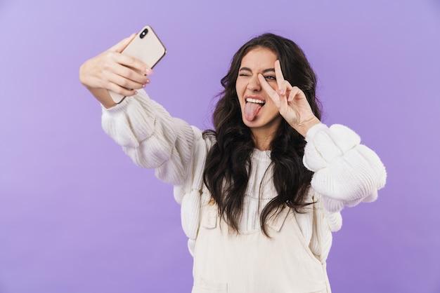 Glückliche optimistische süße junge brünette frau, die isoliert über lila wand posiert, machen ein selfie mit dem handy, das zunge und friedensgeste zeigt.