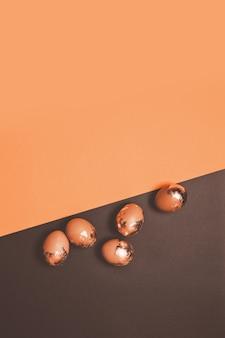Glückliche osterkomposition der goldenen hühnereier verstreut auf einem dunklen hintergrund. vertikales foto