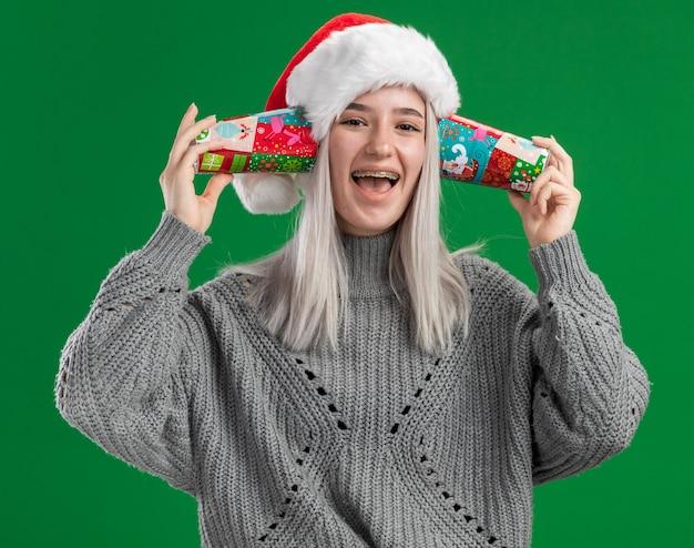 Glückliche oung blonde frau im winterpullover und in der weihnachtsmannmütze, die bunte pappbecher über ihren ohren hält, die fröhlich über grünem hintergrund stehend lächeln