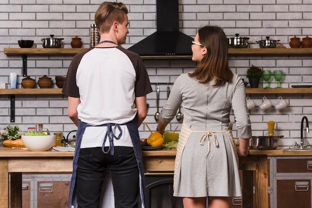 Glückliche paare, die am tisch in der küche kochen