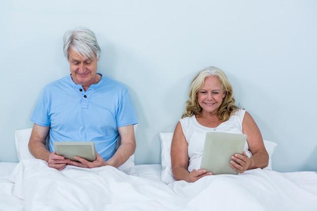 Glückliche paare im ruhestand, die digitale tabletten verwenden