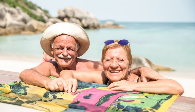 Glückliche paare im ruhestand, die für reisefoto am tropischen strand aufwerfen