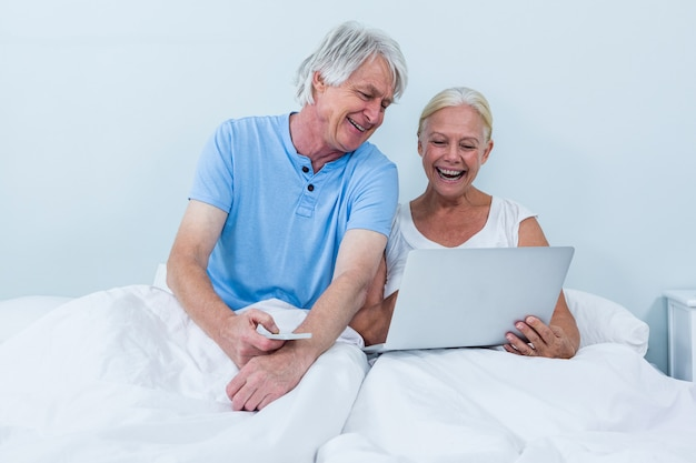 Glückliche paare im ruhestand unter verwendung des laptops beim sitzen auf bett