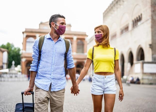 Glückliche paare von touristen, die eine maske tragen, um sich vor covid-19 zu schützen, gehen in der stadt und halten hände und koffer. neues normales reisekonzept.