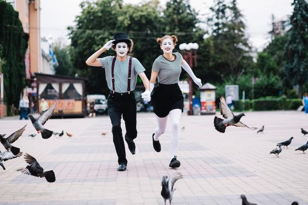 Glückliche pantomimepaare, die auf pflasterung laufen