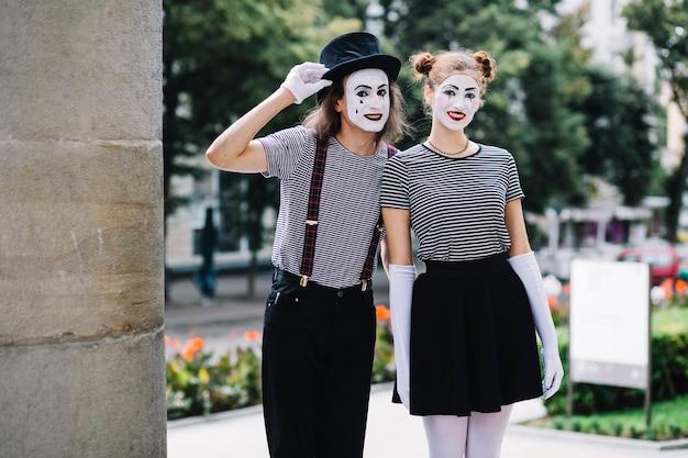 Glückliche pantomimepaare, die im park stehen