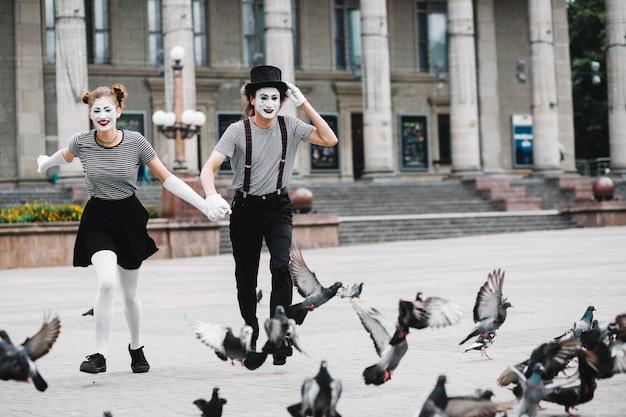 Glückliche pantomimepaare, die nahe fliegentauben laufen