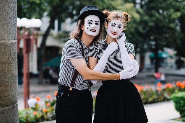 Glückliche pantomimepaare, die sich umfassen