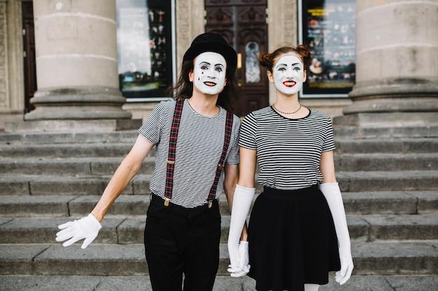 Glückliche pantomimepaare, die vor treppenhaus stehen