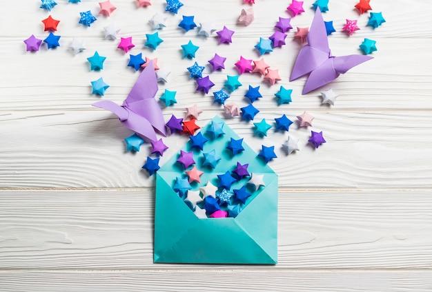Glückliche papiersterne und schmetterlinge des bunten papierorigamis im blauen umschlag auf weißem holz