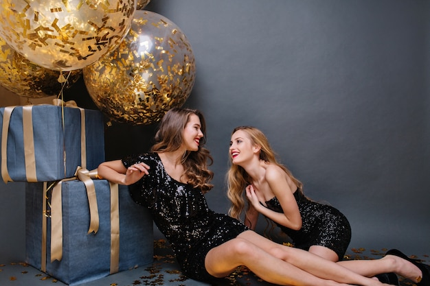 Glückliche party momente zwei attraktive junge frauen, die auf boden nahe großen geschenken chillen. luxuskleider, langes lockiges haar, ausdruck von bestimmtheit, große feste, freunde, glück.