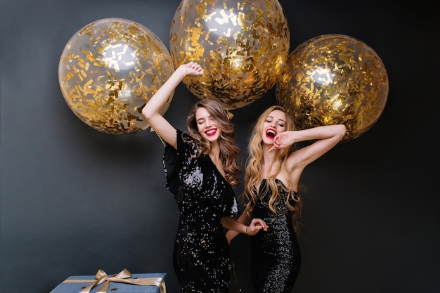 Glückliche partymomente von zwei modischen lustigen jungen frauen. luxuriöses schwarzes kleid, rote lippen, langes lockiges haar, strahlende stimmung, spaß, große luftballons mit goldenen lametta.