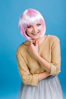 Glückliche partyzeit der jungen attraktiven frau im grauen tüllrock. goldener pullover, geschnittenes rosa haar, strahlendes make-up, ausdruck der bestimmtheit, lächeln, neujahr feiern, geburtstag.