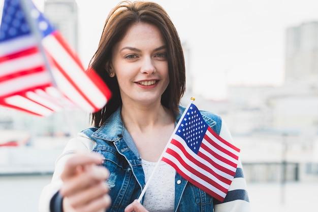 Glückliche patriotische frau, die amerikanische flaggen zeigt