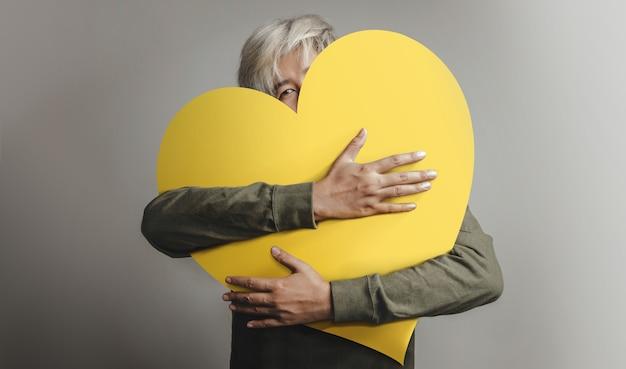 Glückliche person, die sich selbst umarmt und ein großes herz umarmt
