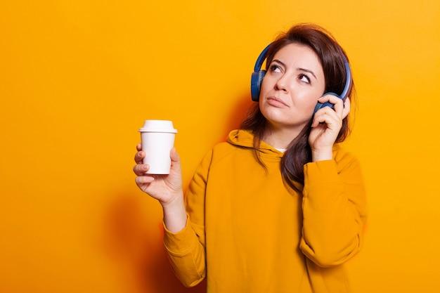 Glückliche person mit einer tasse kaffee, die musik über das headset hört
