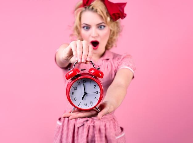 Glückliche pin-up-frau mit uhr. überraschte pin-up-frau im roten kleid hält rote uhr. dame im pin-up-stil. retro-stil. zeit sparen konzept. sommerschlussverkauf. rabatt. auf rosa hintergrund isoliert.