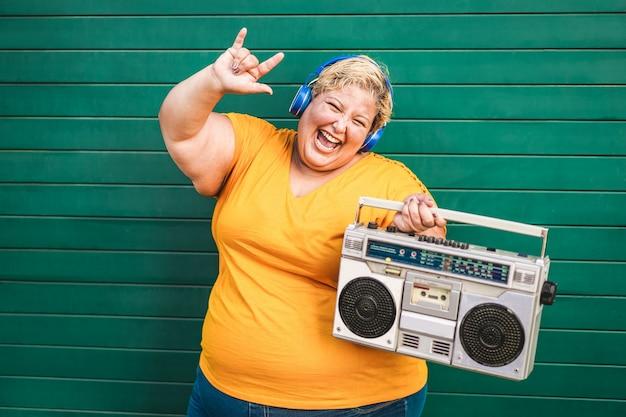 Glückliche plus-size-frau tanzt und hört rockmusik mit vintage-boombox