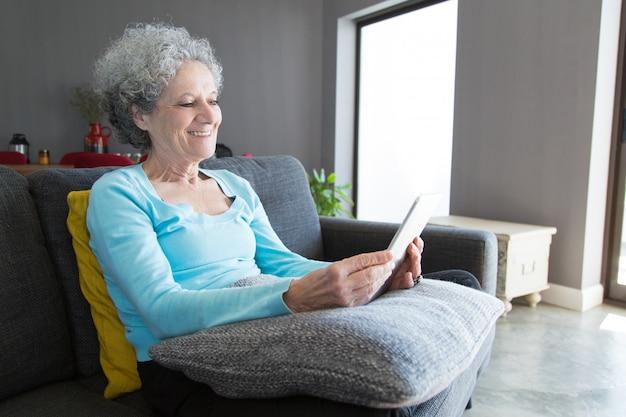 Glückliche positive ältere frau, die tablette verwendet