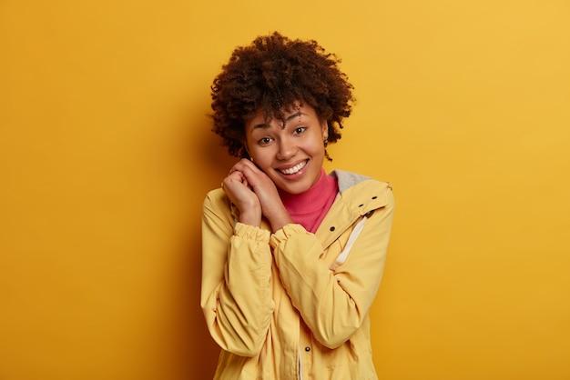 Glückliche positive afroamerikanische frau lächelt sanft, lehnt sich an die hände, freut sich über komplimente, trägt anorak, beobachtet etwas angenehmes, bleibt auf der positiven seite und drückt begeisterung und bestimmtheit aus