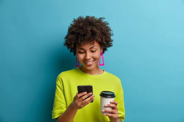 Glückliche positive ethnische junge frau tippt nachricht oder wählt telefonnummer am telefon, trinkt kaffee zum mitnehmen, verwendet mobile online-anwendung, sucht im internet, liest blog und chattet in sozialen netzwerken