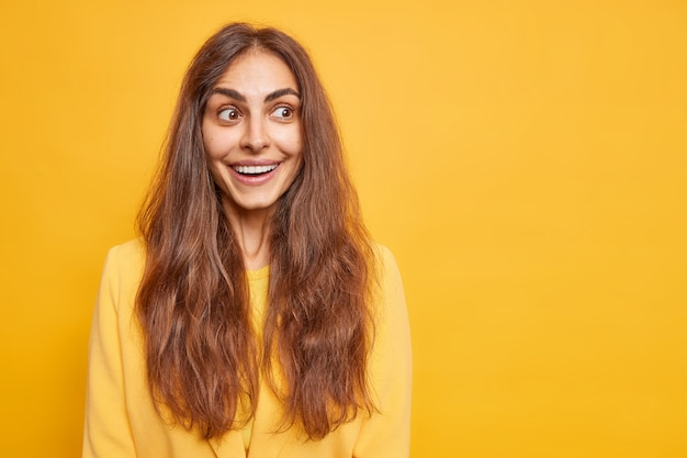 Glückliche positive frau mit langen dunklen haaren lächelt angenehm fokussiert beiseite hat neugierige fröhliche ausdrucksmodelle gegen lebendige gelbe wandleerkopienraum zu ihrer information emotionen konzept