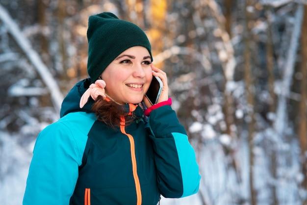Glückliche positive junge frau, die am kalten kalten sonnigen wintertag im park geht und auf ihrem handy spricht