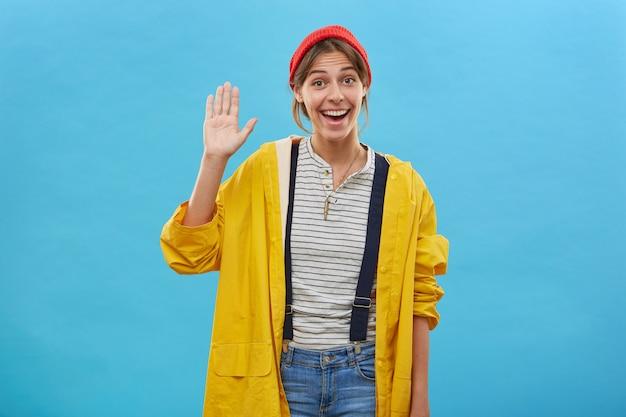Glückliche positive junge frau gekleidet beiläufig winkend mit ihren palmengrußfreunden, die freundliches zeichen lokalisiert über blauer wand zeigen. lächelnde angenehm aussehende frau, die vor vergnügen ihre hand hebt