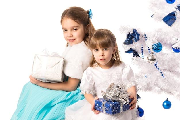 Glückliche positive kleine mädchenschwestern, die geschenkboxen halten, während sie nahe einem weißen künstlichen weihnachtsbaum auf einem weißen hintergrund sitzen